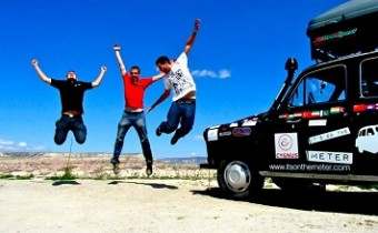 three men jumping by a taxi
